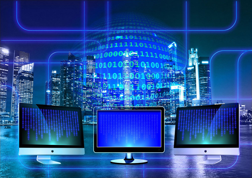 Image of three monitors and binary code on cityscape background by Pixabay user geralt.
